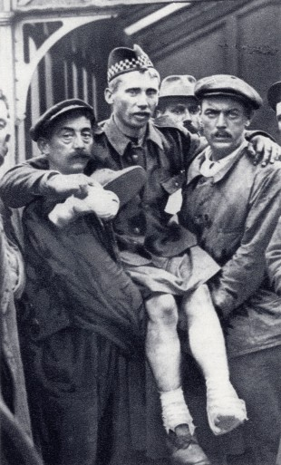 An Illustrated War News picture of porters at Boulogne, France, carrying a soldier who has been wounded in both feet to an ambulance train.