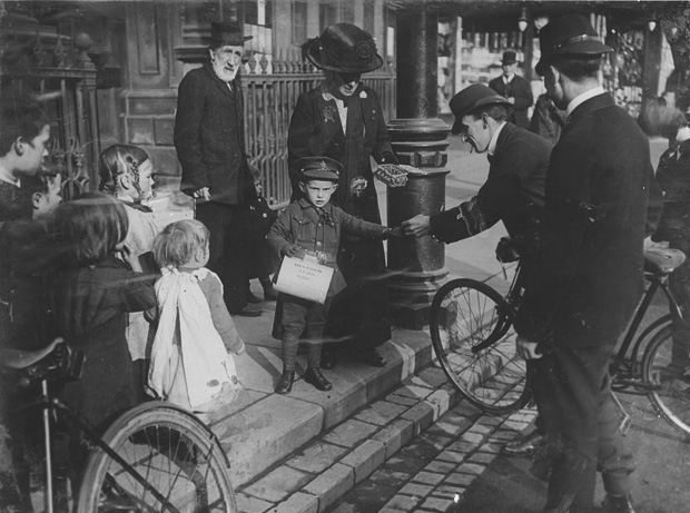 A postman buys a Belgian flag from a young refugee on Darlington's High Row, probably on Saturday, October 24, 1914